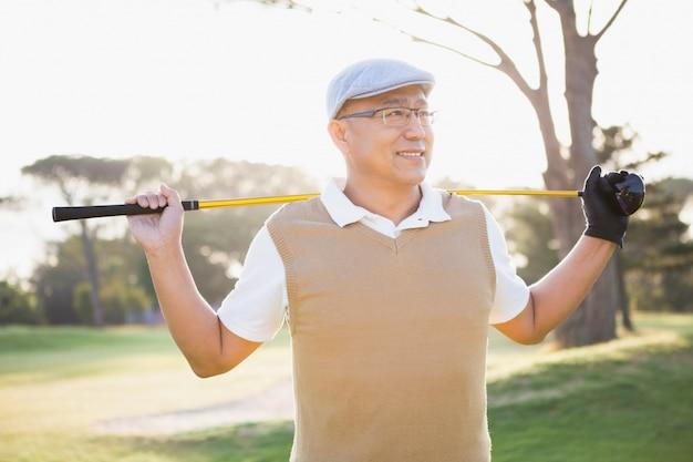 Sportler, der mit seinem golfschläger wegschaut