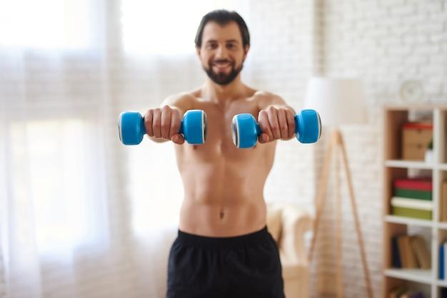 Sportler, der muskeln durch dummköpfe aufpumpt