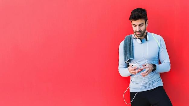 Sportler, der smartphone auf rotem hintergrund verwendet