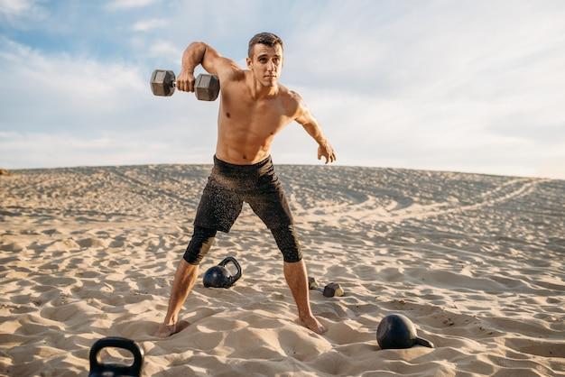 Sportler, der übungen mit gewichten in der wüste am sonnigen tag tut. starke motivation im sport, krafttraining im freien
