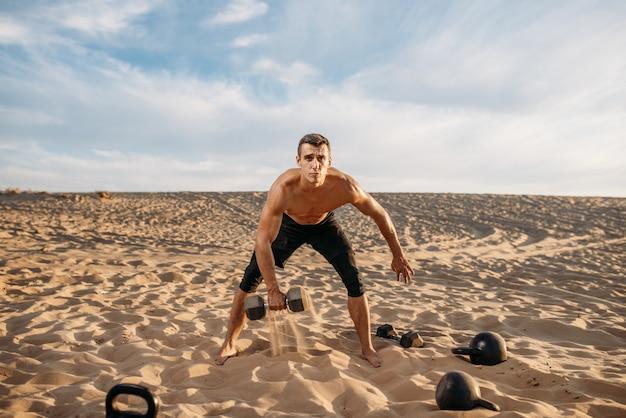 Sportler, der übungen mit hanteln in der wüste am sonnigen tag tut. starke motivation im sport, krafttraining im freien