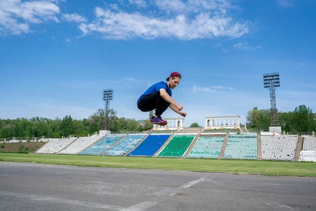 Sportler des jungen mannes üben hochsprungfliege in der luft am stadion an sommertagen