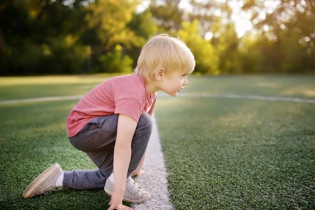 Sportler des kleinen jungen, der fertig wird, im schulstadion einen abstand zu laufen.