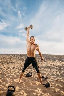 Sportler, die am sonnigen tag übungen mit gewichten in der wüste machen. starke motivation im sport, krafttraining im freien