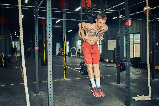 Sportler, die muskelaufbauübungen auf den gymnastikringen machen.