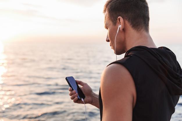 Sportler draußen am strand, der musik mit kopfhörern hört.