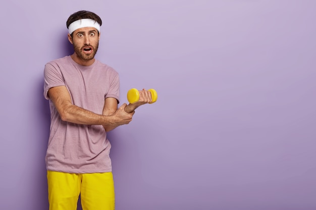 Sportler hält handgelenk, hebt hantel, trainiert muskeln, trägt freizeitkleidung, hat einen athletischen körper