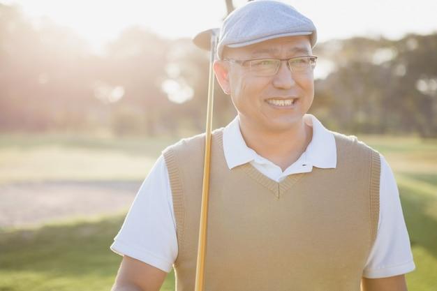 Sportler hält seinen golfschläger und schaut weg