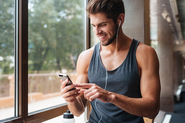 Sportler im fitnessstudio mit telefon. lächelnd