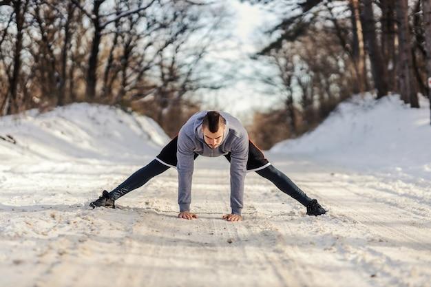 Sportler in form, die auf verschneiten pfaden in der natur stehen und aufwärm- und dehnungsübungen machen. winterfitness, flexibilität, gesundes leben