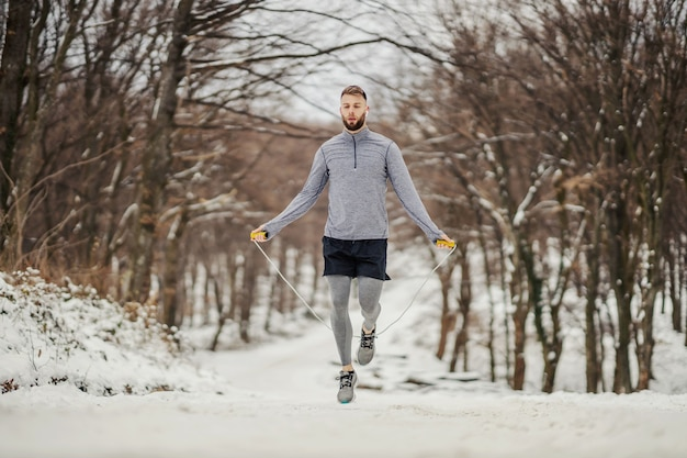 Sportler in form springseil in der natur auf schnee im winter. winterfitness, gesunde gewohnheiten, kühles wetter