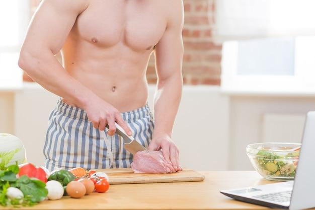 Sportler kocht in der küche, verwendet gemüse und verschiedene fleischsorten zum kochen des abendessens und sieht sich online-kochkurse an
