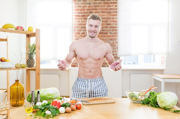 Sportler kocht in der küche, verwendet gemüse und verschiedene fleischsorten zum kochen des abendessens