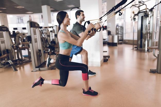 Sportler machen übungen in einem modernen fitnessstudio mit modernen simulatoren