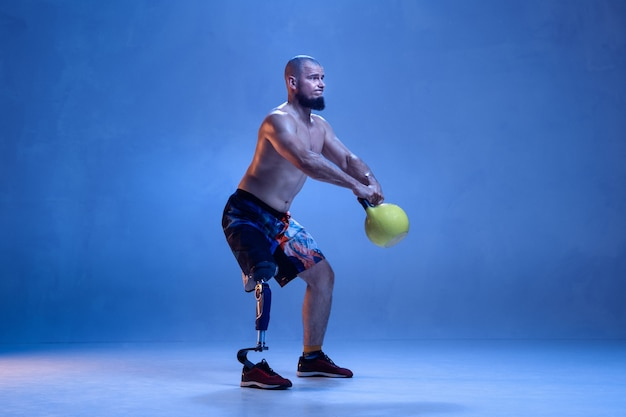 Sportler mit behinderungen oder amputierten isoliert auf blauer wand. professioneller männlicher sportler mit beinprothesentraining mit gewichten in neon. behindertensport und überwindung, wellnesskonzept.