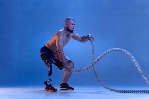 Sportler mit behinderungen oder amputierten isoliert auf blauer wand.