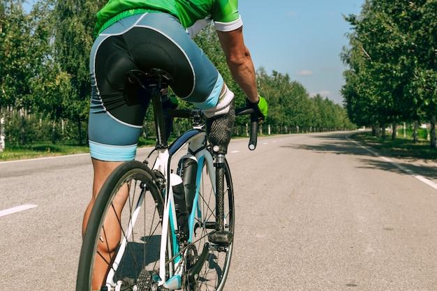 Sportler mit behinderungen oder amputierten trainieren im radsport an einem sonnigen sommertag. professioneller männlicher sportler mit beinprothese, die im freien übt. behindertensport und gesunder lebensstil konzept.
