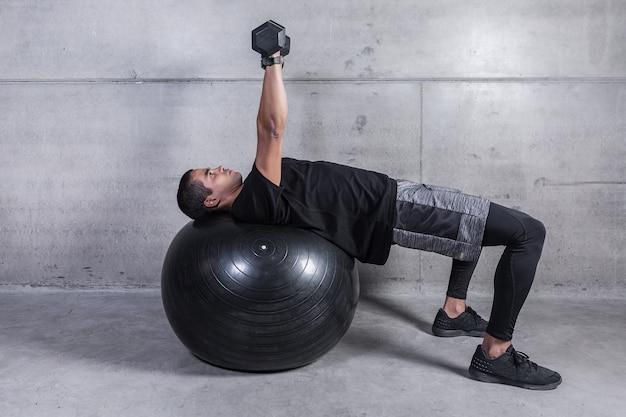 Sportler mit dummköpfen auf schwarzem medizinball