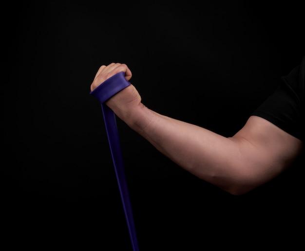 Sportler mit einem muskulösen körper in schwarzer kleidung machen körperliche übungen mit lila gummi