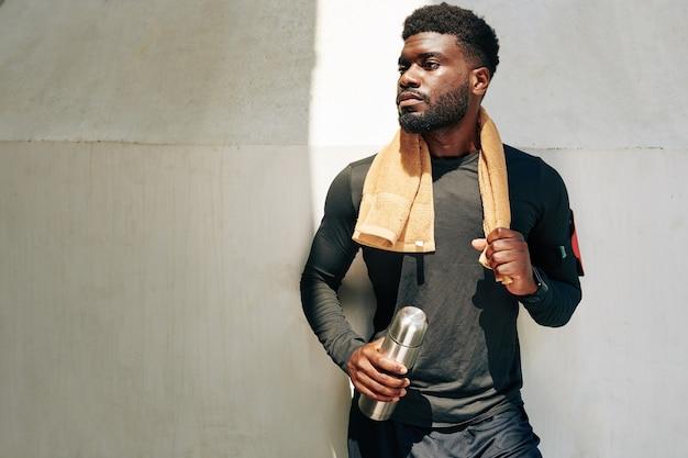Sportler mit handtuch und thermoskanne