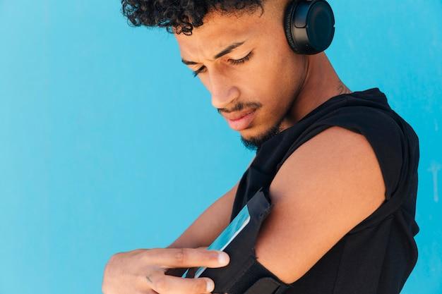 Sportler mit kopfhörern unter verwendung des telefons im armkasten