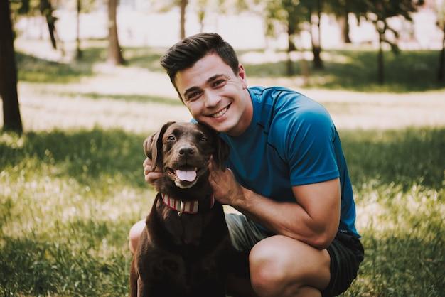 Sportler mit seinem hund im grünen stadtpark