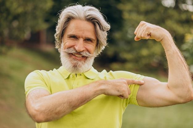 Sportler mittleren alters, der auf seinen bizeps zeigt