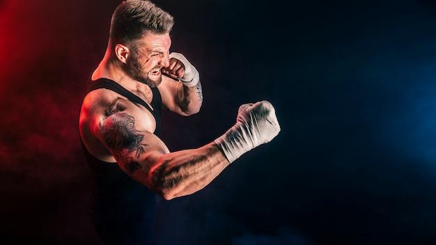 Sportler muay thai boxer, der auf schwarzer wand mit rauch kämpft. sportkonzept.