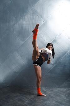 Sportler muay thai boxerin posiert im trainingsstudio auf schwarzem hintergrund.
