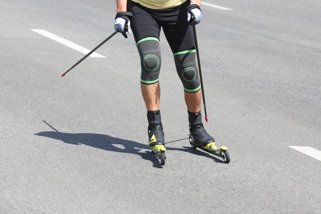 Sportler-rollski auf dem asphalt auf der stadtstraße
