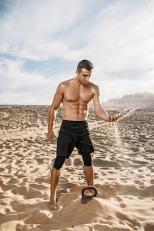 Sportler sitzen auf sand nach dem training in der wüste am sonnigen tag. starke motivation im sport, krafttraining im freien