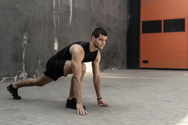 Sportler startet seinen sprint auf einer grauen industriewand