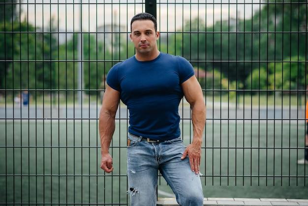 Sportler steht in der nähe des sportplatzes. bodybuilding