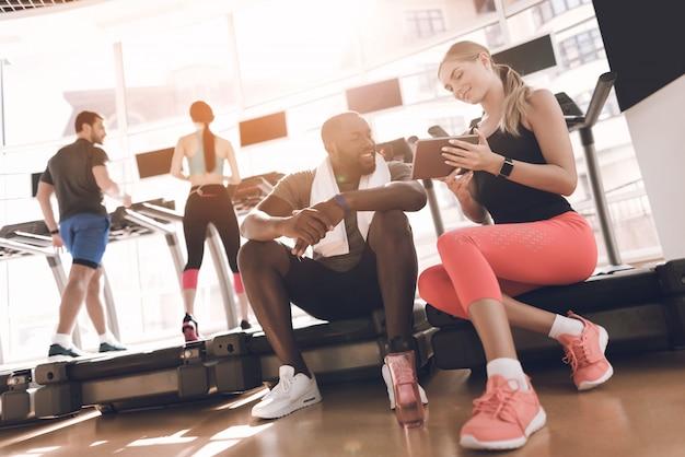 Sportler trainieren im hellen fitnessstudio mit modernen laufbändern.