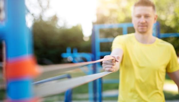 Sportler trainieren mit elastischem gummiband nahaufnahme auf band close