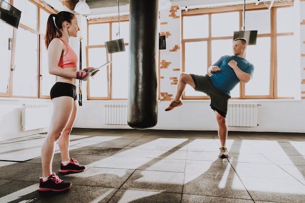 Sportler trainiert in der turnhalle mit trainer