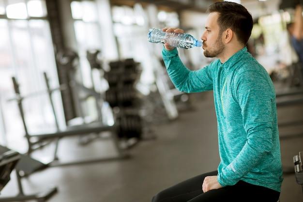 Sportler trinkt wasser aus der flasche im fitnessstudio und ruht sich aus