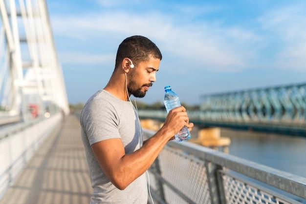 Sportler trinkwasser beim training