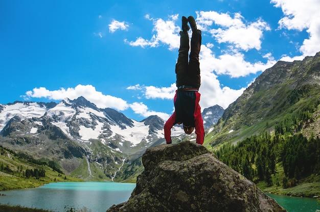 Sportler turner machen gefährliche übungen auf felsen vor dem hintergrund einer wunderschönen berglandschaft mit schneebedeckten gipfeln und türkisfarbenem see und blauem himmel mit weißen wolken. gymnastikübungen machen