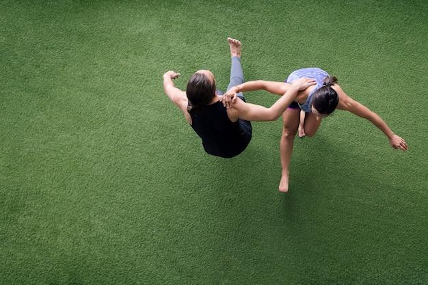 Sportler und sportlerin machen kniebeugen in der draufsicht des fitnessstudios