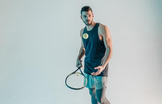 Sportler werfen tennisball hoch und halten schläger. der junge bärtige europäische tennisspieler konzentriert sich auf das spiel. auf grauem hintergrund mit türkisfarbenem licht isoliert. studio-shooting. platz kopieren