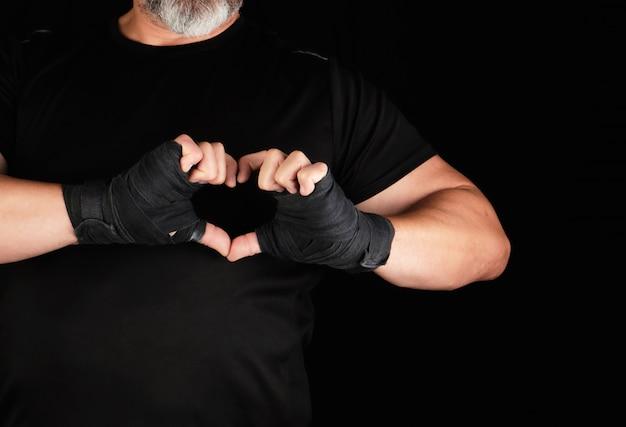 Sportler zeigt das symbol des herzens, die handfläche eines mannes ist mit einem schwarzen sportverband umwickelt