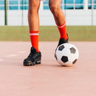 Sportlerfüße, die fußball am stadion spielen