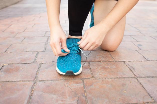 Sportlerin binden ihre schuhe werden zum laufen im freien fertig