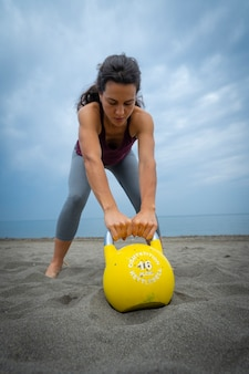 Sportlerin, die am strand mit kesselglocken trainiert