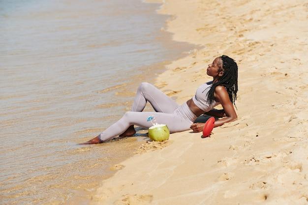 Sportlerin, die am strand ruht