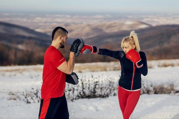 Sportlerin, die am verschneiten wintertag mit ihrem lehrer mit boxhandschuhen in der natur kämpft. boxen, winterfitness, outdoorfitness