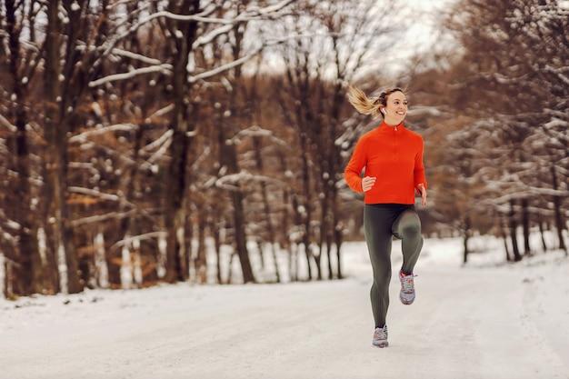 Sportlerin, die an einem verschneiten wintertag in der natur joggt. kaltes wetter, schnee, gesundes leben, fitness, gesunde gewohnheiten, wald