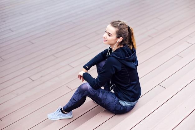 Sportlerin, die auf treppe beim hören musik während der rüttelnden übung sitzt