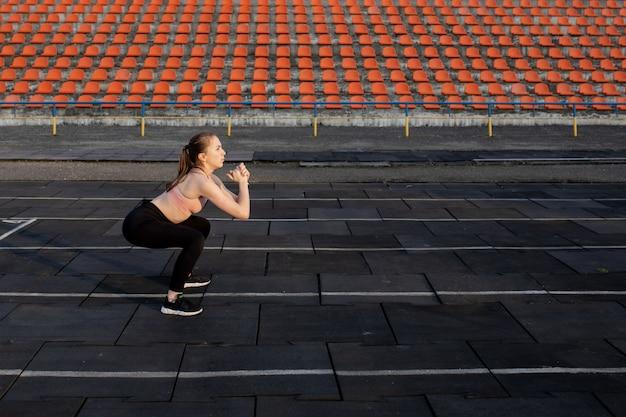 Sportlerin, die beine für cardio-training vorbereitet. fitness-läufer, der aufwärmroutine tut. frau läufer im freien aufwärmen. sportler, der sich auf einer laufbahn in einem stadion ausdehnt und aufwärmt